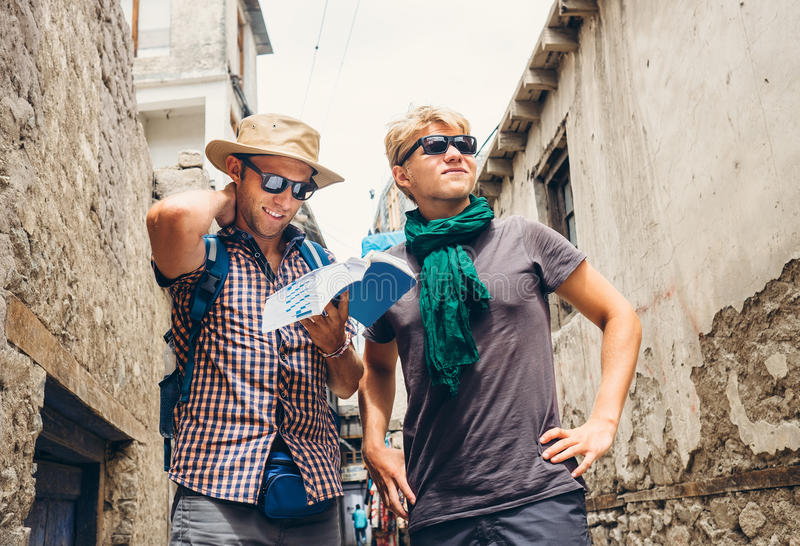 Two tourists try to navigate with guidebook on unknown asian street royalty free stock photos