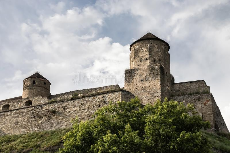 Two towers and stone walls of the medieval Kamianets-Podilskyi fortress of the XVI century on a hill. royalty free stock photography