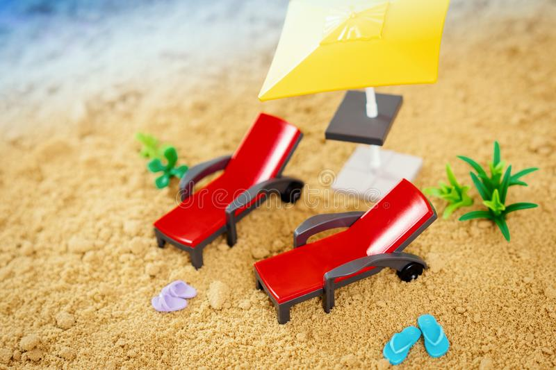 Two toy deckchairs and small blue flip-flops on the sand royalty free stock photography
