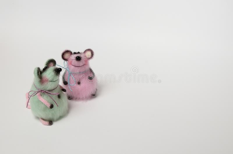 Two toy knitted mice pink and turquoise on a white background. Symbol of 2020. Copy space stock photo