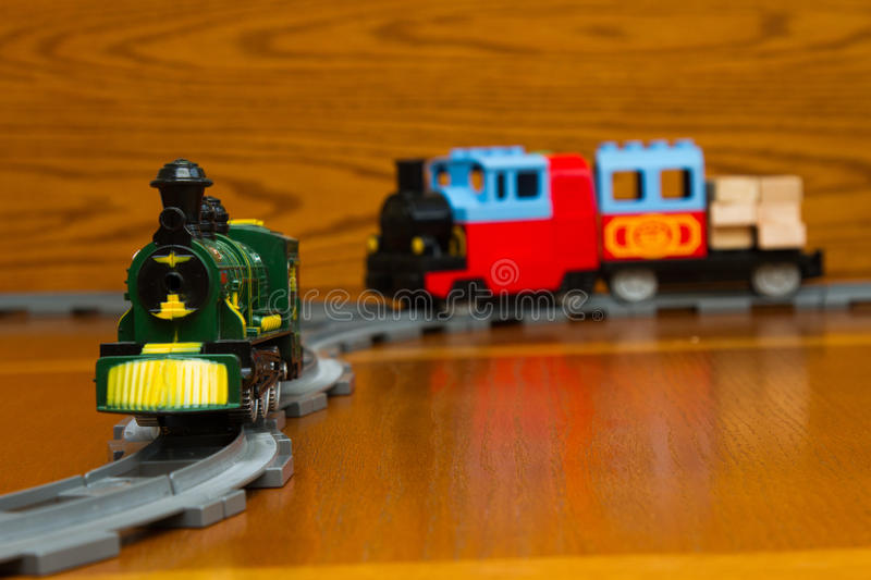 Two toy trains on the gray Rails. The toy train goes on rails. On a brown background stock photos