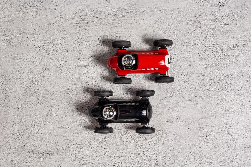 Two toy vintage racing cars red and black racing on a textured plain surface stock photo