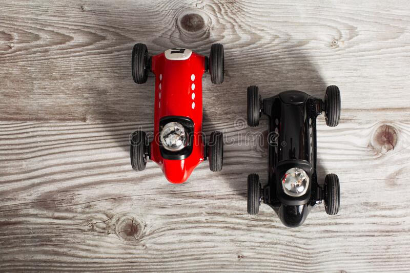 Two toy vintage racing cars red and black racing on a wooden surface royalty free stock photos