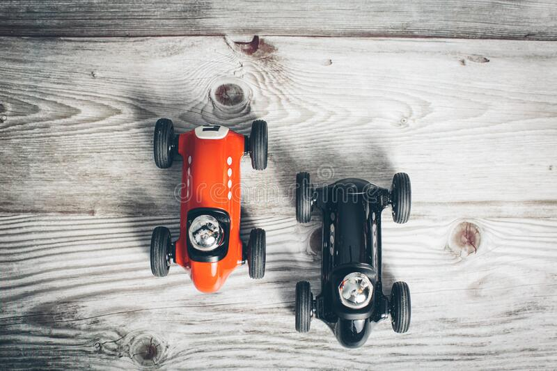 Two toy vintage racing cars red and black racing on a wooden surface stock image
