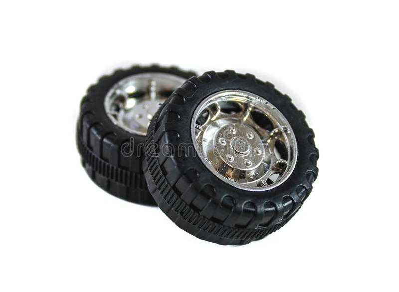 Two toy wheels from the car, black and metal color on a white background. Two toy wheels from a car, black and metallic color on a white background, stacked one royalty free stock photo