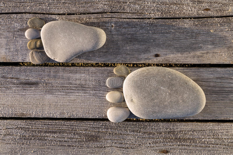 Two traces of pebbles over wooden planks. Two traces of feet made of pebbles over wooden planks royalty free stock photos