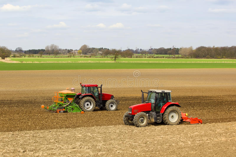 Two tractors. Two red tractors cultivating and sowing spring barley in a field in an agricultural landscape in springtime royalty free stock images