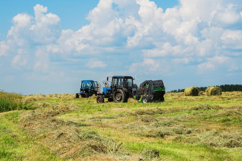 Two tractors in the field. Two tractors with equipment for hay work in the field royalty free stock images