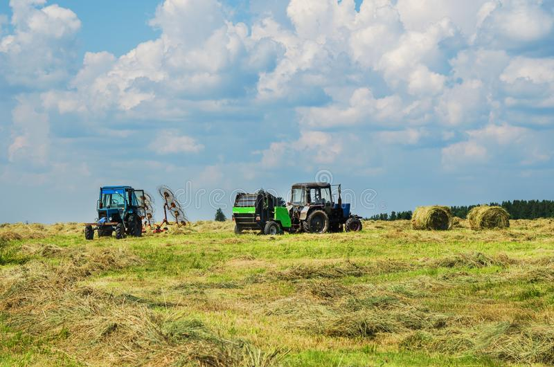 Two tractors in the field. Two tractors with equipment for hay work in the field stock image