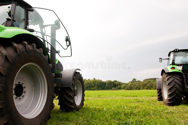 Two tractors. On the green field royalty free stock image
