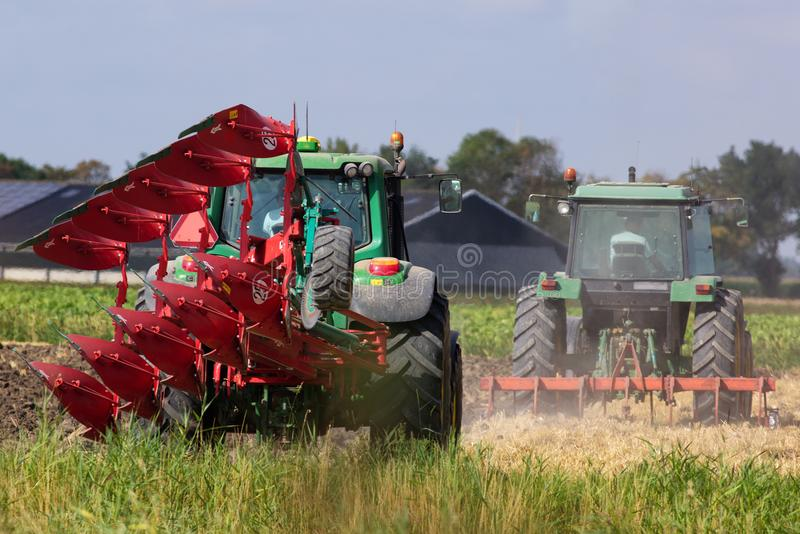 Modern Agriculture. Two tractors. one with a reversible plough working on the land