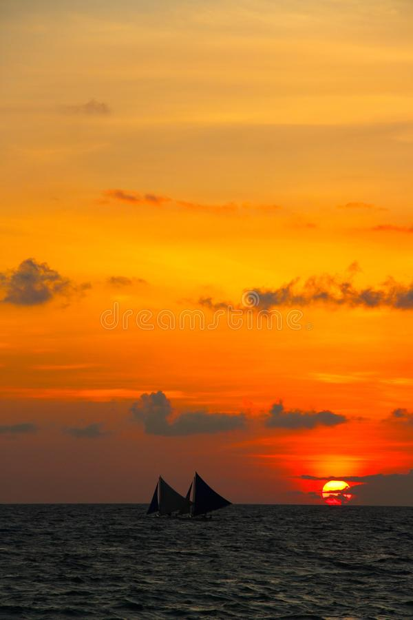 Two traditional sail boats catch the last glimps of the sunset stock photo