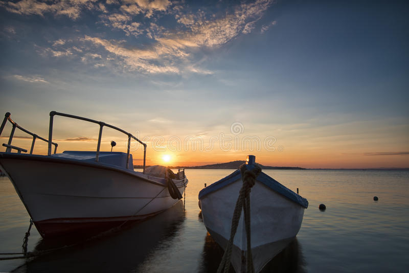 Two traditional wooden fishing boats in the sea. Fishing boats tied up in harbor at the end of the day. Sunset near the Black Sea. Two traditional wooden fishing royalty free stock photography