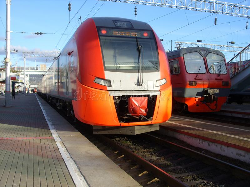 Two trains standing at the station. Two trains stand at the station against the blue sky stock images