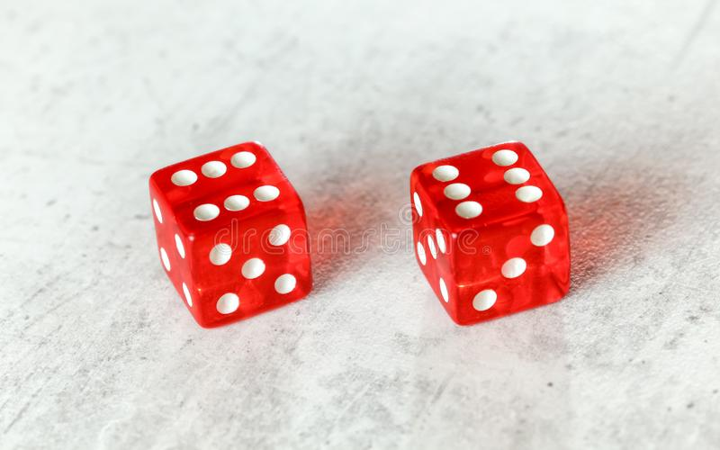 Two translucent red craps dices on white board showing Boxcars or Midnight double number 6.  royalty free stock photo