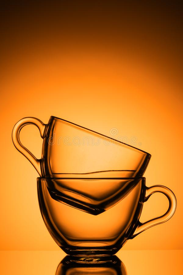 Two transparent glass mugs for tea. Orange background, close-up, vertical layout stock image