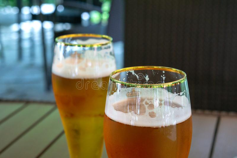 Two transparent glasses of light beer on a wooden table. Soft focus stock image