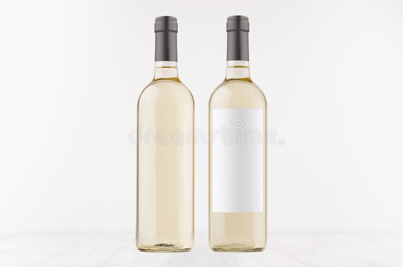 Two transparent wine bottles with blank white label and without label, on white wooden board, mock up. royalty free stock image