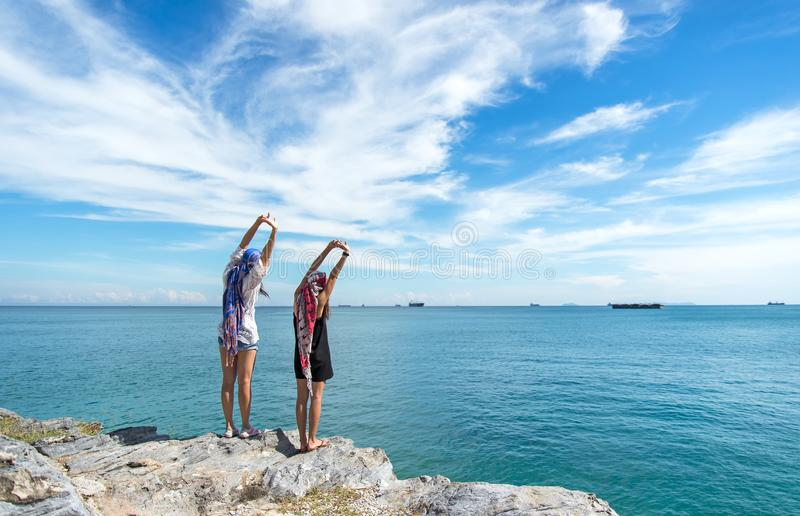 Two traveler young women seeing the beautiful beach and blue sky, so happy and relax. stock photo
