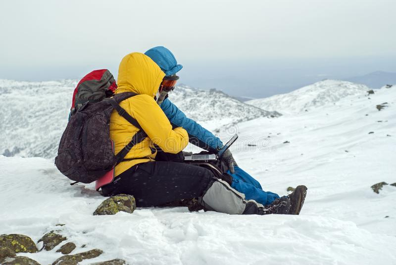 Two travelers sitting with a laptop in winter on top of a mountain. Two travelers are sitting with laptop on top of a winter mountain against a background of a royalty free stock image