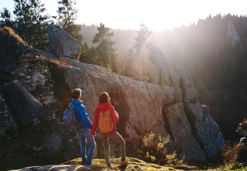 Two travelers standing on the cliff against wooded hills and cloudy sky at sunrise. Couple standing hands up, greeting stock photo