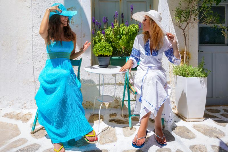 Two traveller woman friends are enjoying the white alleys of the Cyclades islands in Greece stock photo