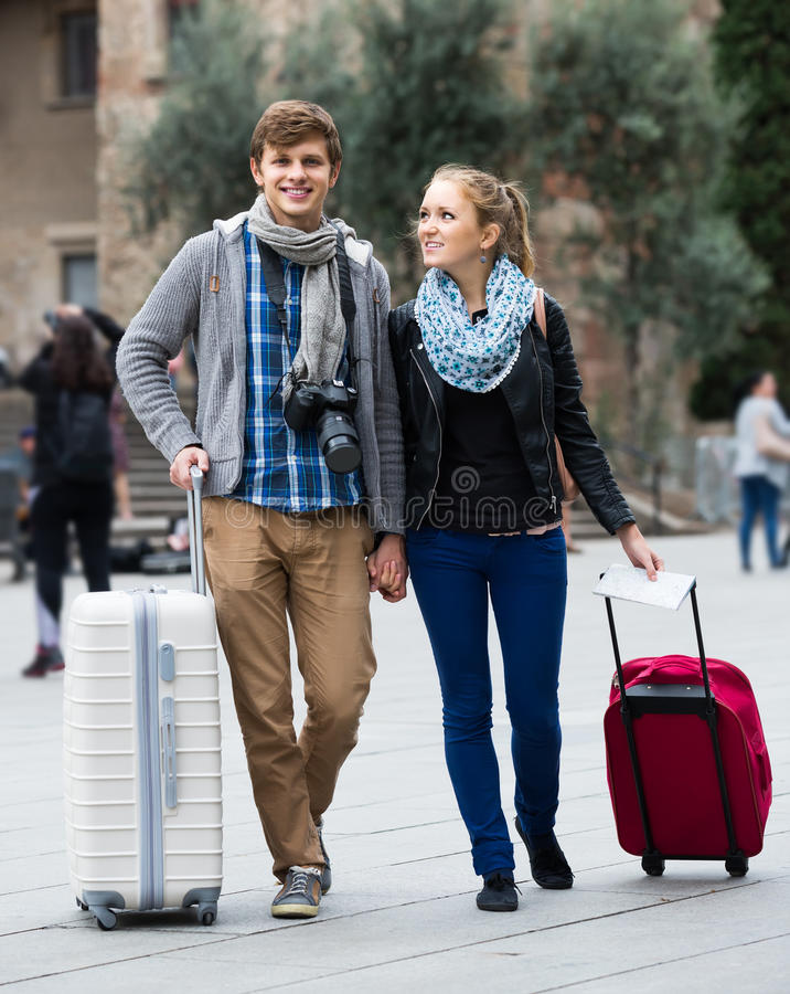 Two travellers with digital camera walking through city street royalty free stock photo