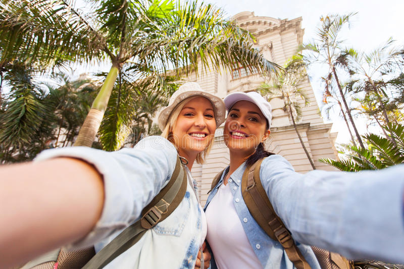 Two travellers selfie. Happy two female travellers taking selfie together royalty free stock images