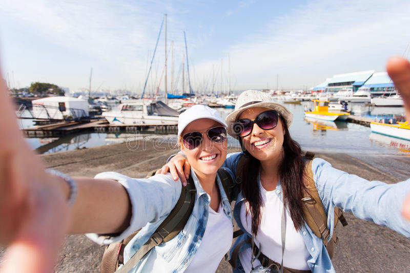 Two travellers selfie. Two happy travellers taking selfie together by the harbor stock photos