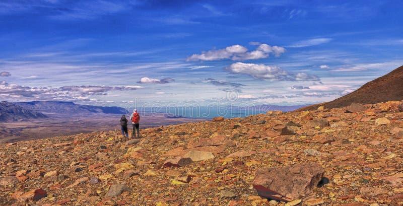 Seeking expansive horizons twixt rock and sky in Patagonia. Two trekkers enjoy distant views of Lago Viedma near El Chalten Patagonia royalty free stock image