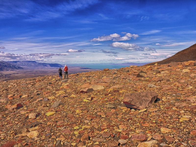 Two trekkers at a rocky viewpoint of Lago Viedma in Patagonia. Two trekkers enjoy distant views of Lago Viedma and the rocky mountain terrain near El Chalten royalty free stock image