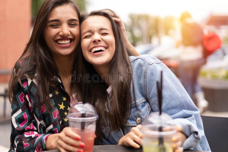 Hipster girlfriends drink cocktail in urban city background stock image