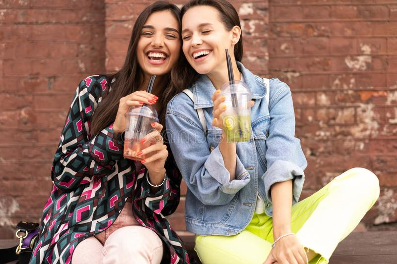 Hipster girlfriends drink cocktail in urban city background royalty free stock photography
