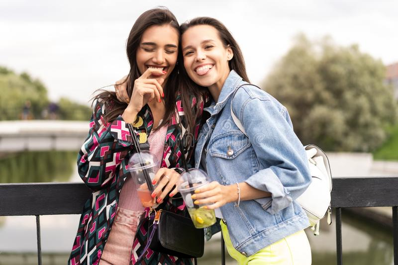 Hipster girlfriends drink cocktail in urban city background stock photo
