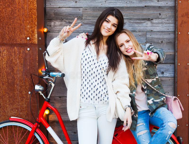 Two Trendy Fashionable Girls with red vintage Bike on old Wooden Background Show a sign of victory. Toned Photo. Modern Youth Life stock photography