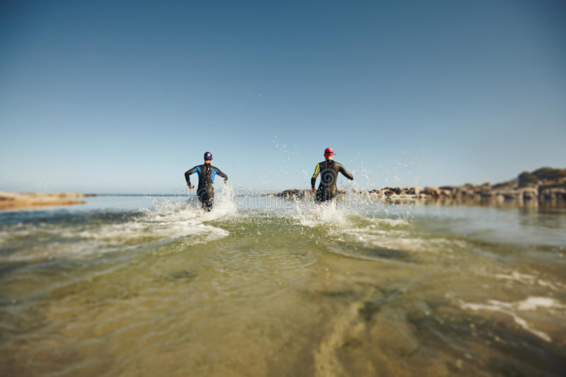 Two triathletes rushing into water for swim portion of race. Participants running into the water for start of a triathlon. Two triathletes rushing into water for stock photo