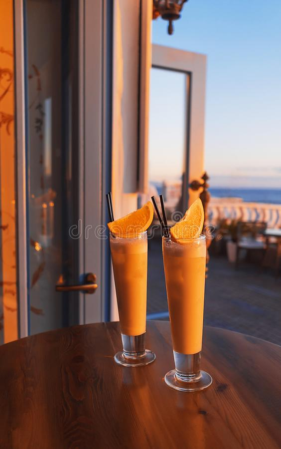 Two tropical cocktails adorned by fresh orange and brightly lit by setting sun on the wooden table of a seafront stock photos