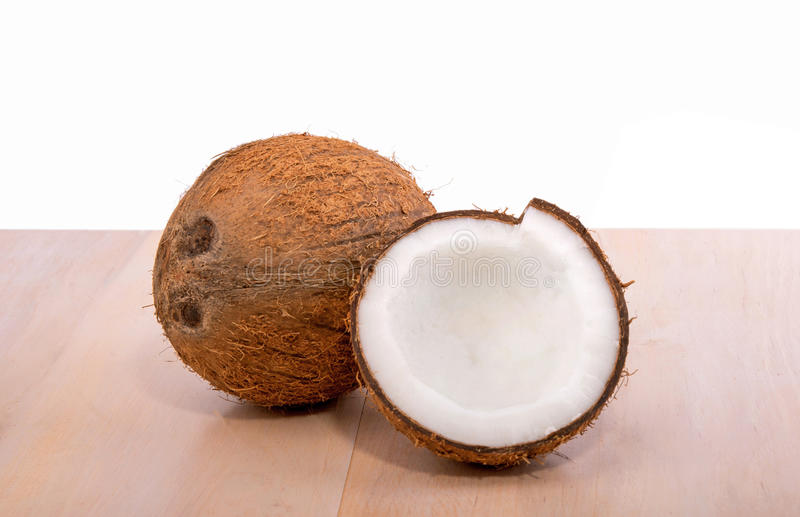 Two tropical coconuts on a wooden table, on a white background. A whole and a cracked coconut. Nature and health concept. stock images