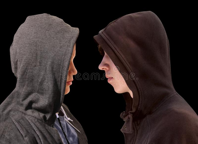 Two troubled teenage boys with black hoodie standing in front of each other in profile isolated on black background - stock stock images