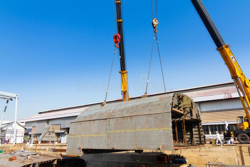 Two truck cranes working over dry dock are lifting ship hull part stock photos