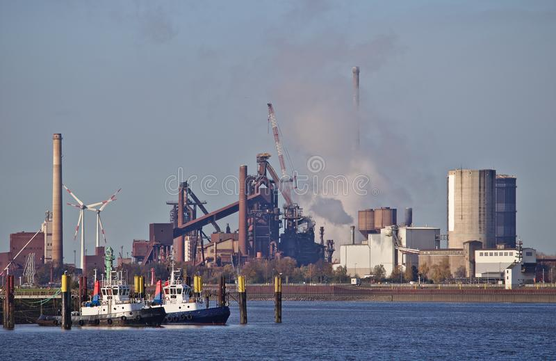 Download Two Tug Boats At Their Moorings With Huge Steel Plant Emitting Clouds Of Smoke And Wind Power Stations In The Background Stock Photo - Image of industry, environment: 103767490