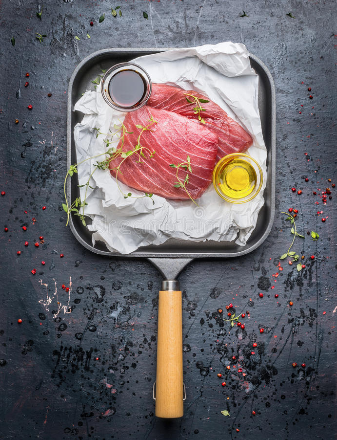 Two tuna steaks in white paper with oil and fresh green seasoning in grill frying pan on dark rustic background, top view. stock image