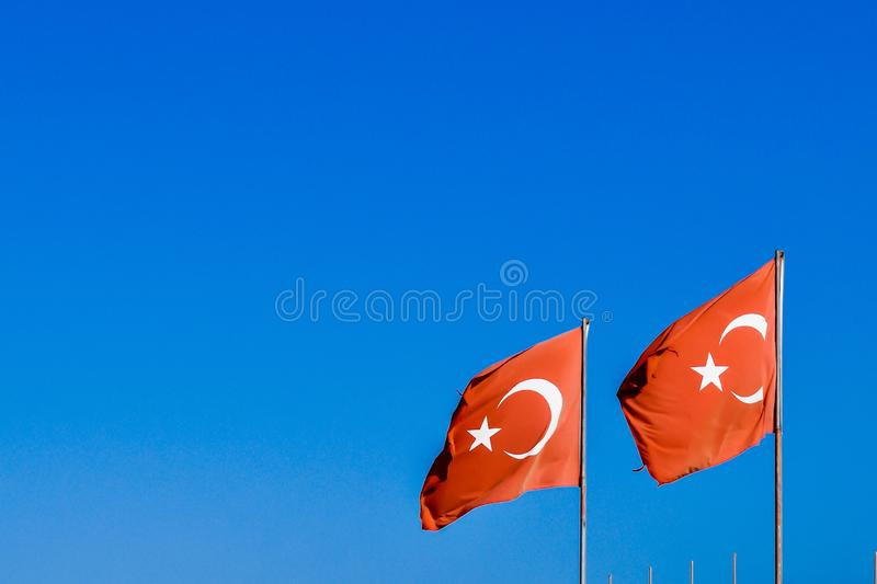 Two Turkish flags waving in the wind. Photograph of a pair of Turkish flags waving in the wind, with a clear bright blue sky as the background stock images