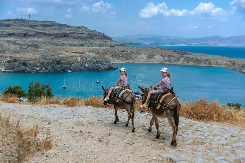 Two twin girls riding donkeys on a mountain road to the sea. Rhodes. Greece stock photo