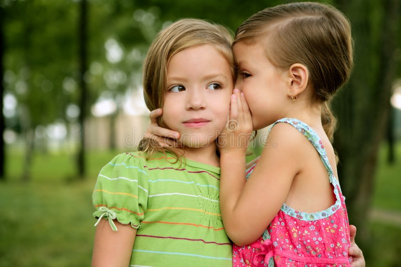 Two twin little sister girls whisper in ear royalty free stock image