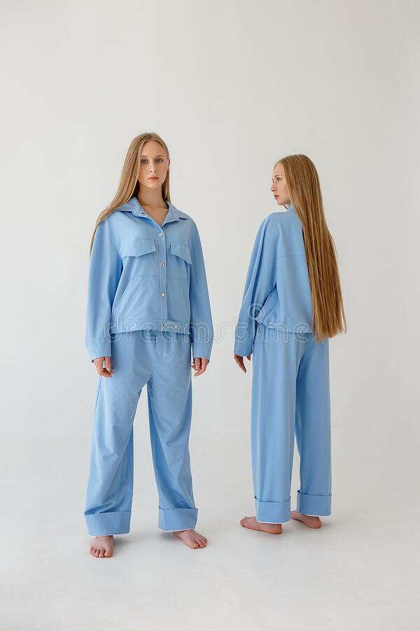 Two twin sisters with long hair posing in oversize clothes on white background stock photography