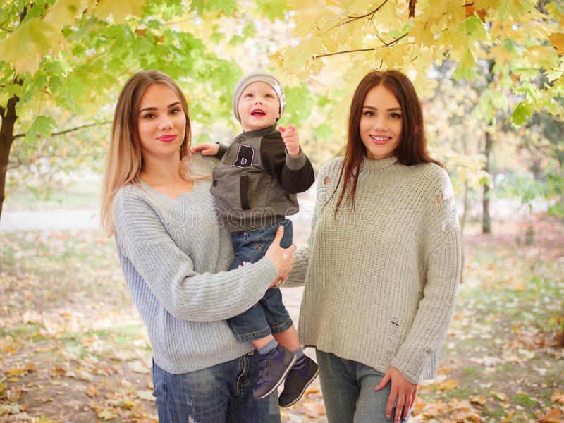 Two twin sisters standing in an autumn park, one of them holding a little boy. stock photography