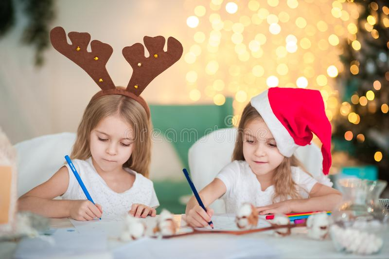 Two twin sisters are writing a letter to Santa Claus for the New Year. A girl with a hat and a girl with reindeer horns. Two twin sisters are writing a letter to stock image