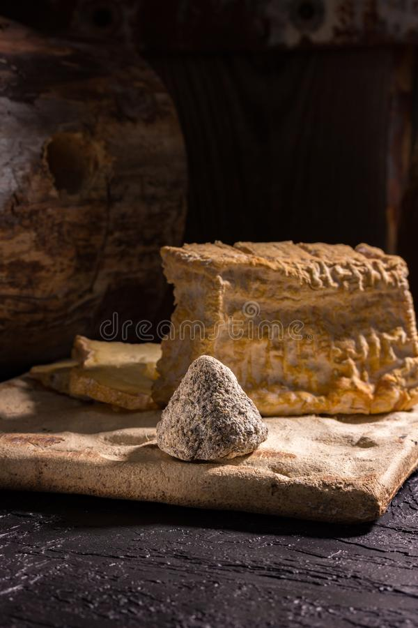 Two types of cheese on a ceramic board on a background of an old log. Rustic style. Appetizing slices of farm craft cheese on the boards royalty free stock image