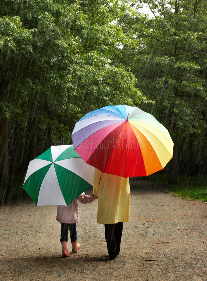 Two umbrellas. Little girl and her mother in the rain